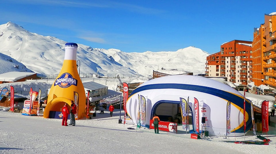 Stand gonflable publicitaire - bouteille gonflable Orangina et stand gonflable ballon de rugby